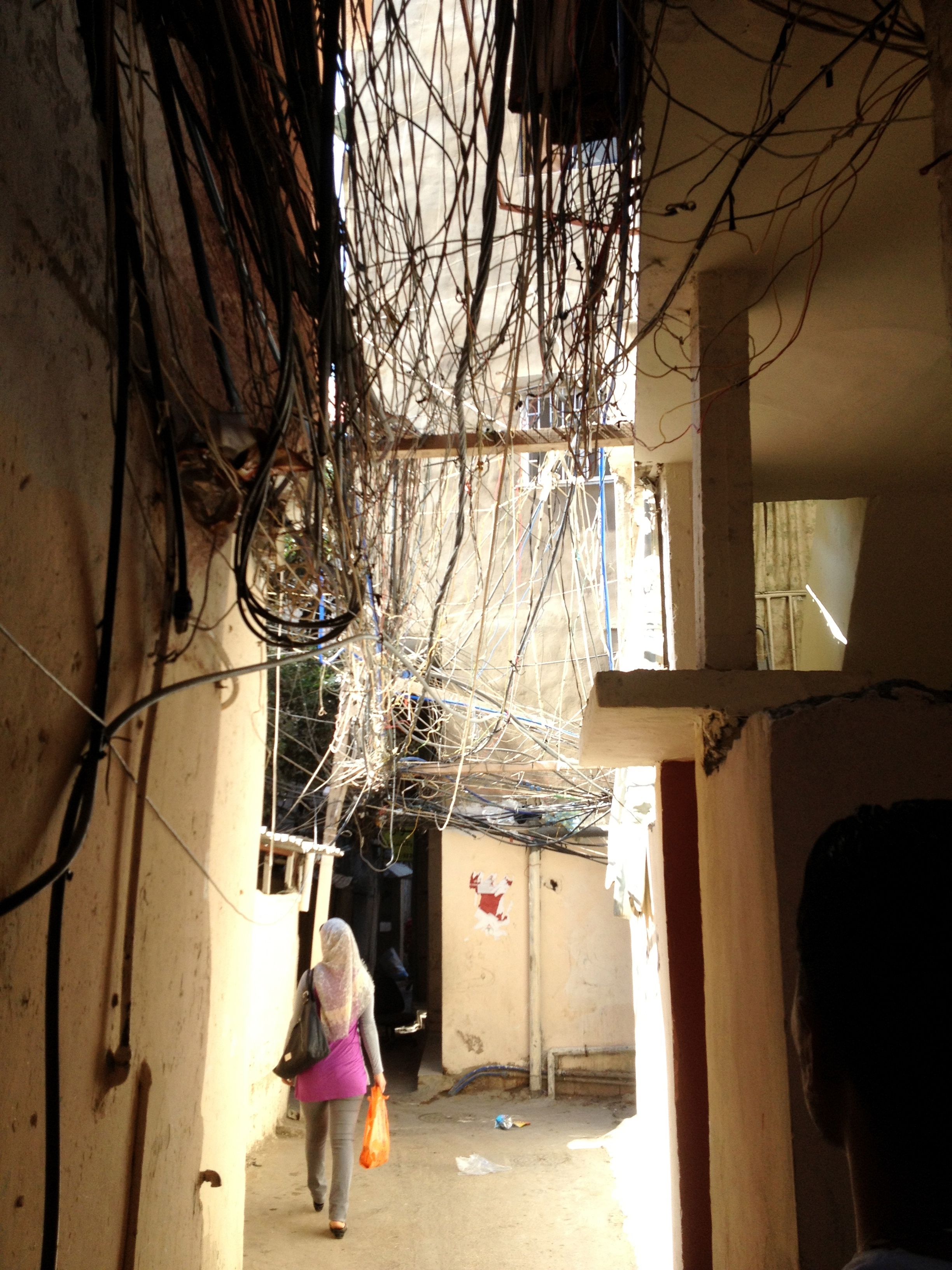 Electric wiring intertwined with water cables - after the young men lifted it into troughs - Burj El Barajneh